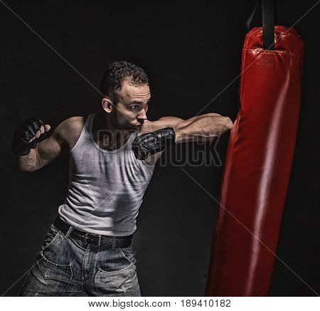 Boxing kick in the red punching pear on black background