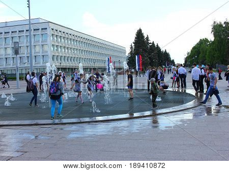 After school graduation ball pupils play with a fountain in the square of the city of Ulyanovsk Russia , May 25, 2017, 16:51:42  , illustrative editorial.
