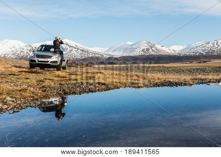 Man explorer in Iceland sitting on the car. Adult man on the bonnet looking through binoculars. Majestic mountains on background reflections on water on foreground. Travel and wanderlust concept