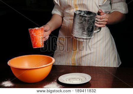 The girl is holding a glass of flour and a flour sieve. Black background. Concept.