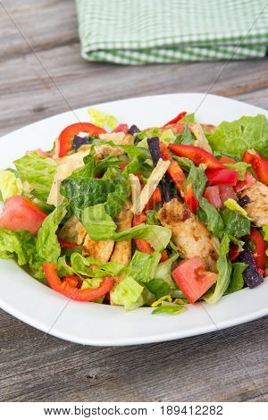 chicken and vegetable summer salad with pepper and tortilla strips