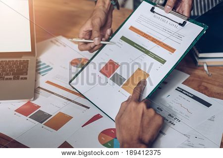 Businessman pointing graph chart with pathner for analyze plans in this mounth. vintage tone.