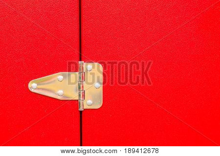 Construction details silver objects concept. Closeup of metal steel hinge on red door