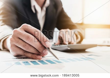 Businessman pen pointing graph chart in this mounth and use calculator for Plans to improve quality next month.