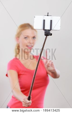 Technology modern photography confidence conept. Happy attractive adult blonde woman taking picture of herself with smartphone on selfie stick.