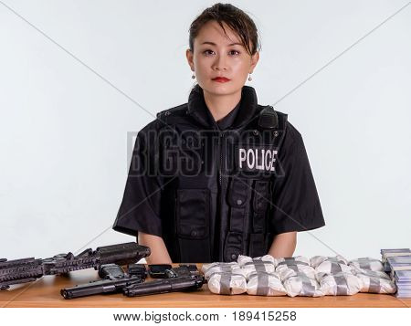 Female Asian Police Officer With Seized Goods