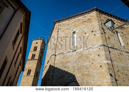 Volterra, Tuscany - May 21, 2017 - Baptistery Of San Giovanni Battista And Tower Of Cathedral