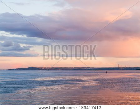 Scenic evening river landscape. Blue and pink sky at sunset. Russia, Saratov city, the Volga river