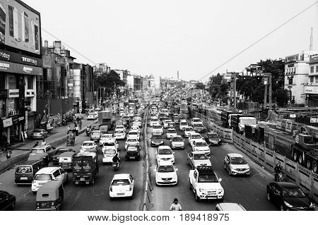 DELHI INDIA - JULY 5 2016: Heavy car traffic in the city center of Delhi India. Buses and construction nearby the road. Various shops cafes restaurants. Black and white
