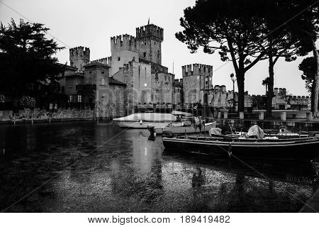Sirmione, Italy. Illuminated Scaliger Castle in Sirmione, Italy - the main attraction of the region at night with reflection in the water. Black and white