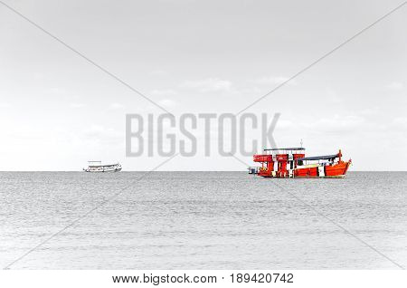 Red Fishing boats are overwhelmingly in the midst of the sea with greyscale background.
