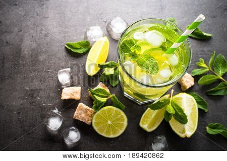 Mojito on black slate background. Summer drink mojito with lime rum mint and ice. Top view copy space.