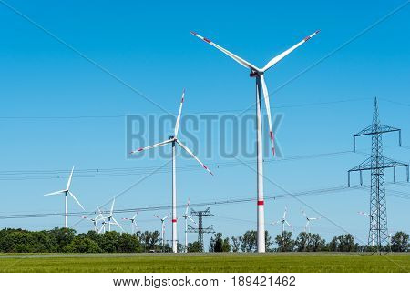 Power transmission lines and windwheels seen in rural Germany