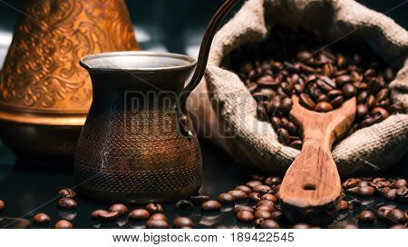 Roasted coffee beans scattered off burlap sack and copper coffee pots on reflective glossy black background. Selective focus