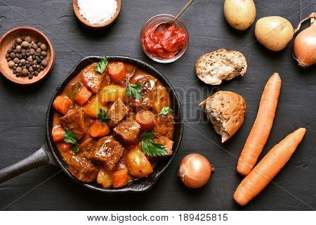 Beef stew in skillet on dark background top view