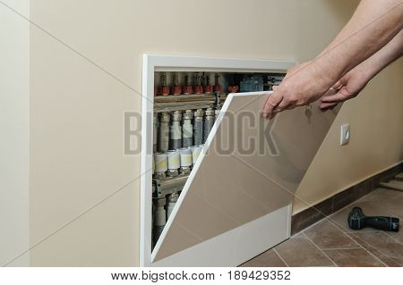 Men's hands are holding a lid of a box of control and distribution of heat in the house.