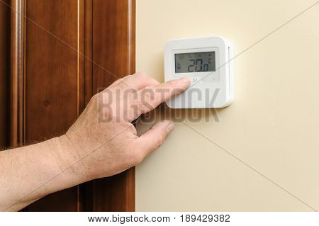 Man is changing settings of a thermostat. His finger is pressing a button.