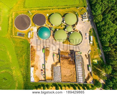 Aerial view over biogas plant and farm in green fields. Renewable energy from biomass. Modern agriculture in Czech Republic and European Union.