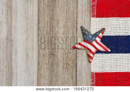 USA flag star with red white and blue pip burlap ribbon on weathered wood background with copy space for your message