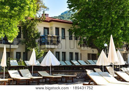 Sunny Hotel Resort with luxury blue swimming pool palm trees umbrellas and sunbeds in Turkey. Rich vacation on the sunny resort.