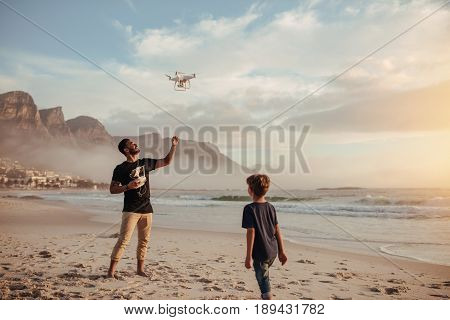 Father And Son Operating Drone By Remote Control At Beach