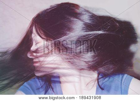 Girl with long dark hair shakes her head, dancing, fun. Photo in vintage colors