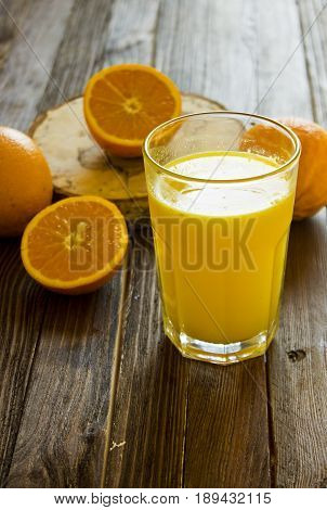Detox diet with orange juice. A glass of orange juice and fresh oranges stand on a wooden table.
