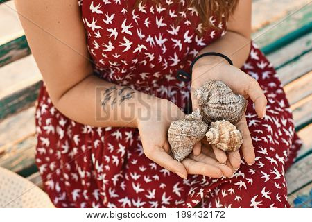 Young woman wearing a red dress with a bird pattern and a tattoo is holding three beautiful seashells with her hands over the lap while sitting on the wooden bench