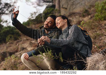 Young Couple Out On Hike In Mountains Taking Selfie