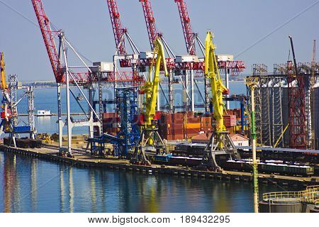 The port in the city of Odessa Ukraine - May 4 2017. Cargo containers in the port territory are unloaded by cranes from the ship. Seaport.