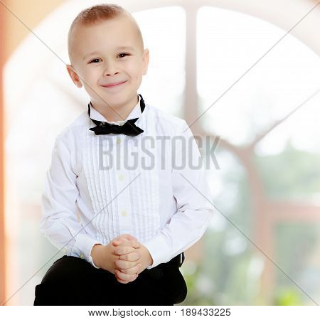 Beautiful , elegant little boy in black pants , white shirt and black tie.In a room with a large semi-circular window.