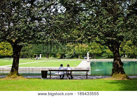 Elderly couple sits on a bench in the park of the Hellbrunn palace. The beautiful park with a pond and trees in which people walk