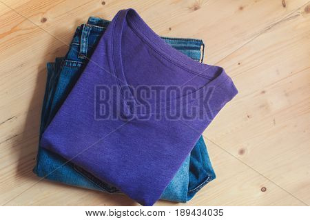 Men's casual clothing. Violet t-shirt and blue denim jeans on wooden table. Fashion, clothing background.