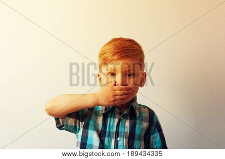 Sad little boy staying against white wall and closing his mouth with hands. Portrait of unhappy caucasian child on white background. Frustration and depression. Abused child.