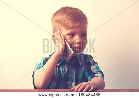 Little caucasin boy sitting at the table and talking on the phone. Cute child using smartphone. Technology concept.