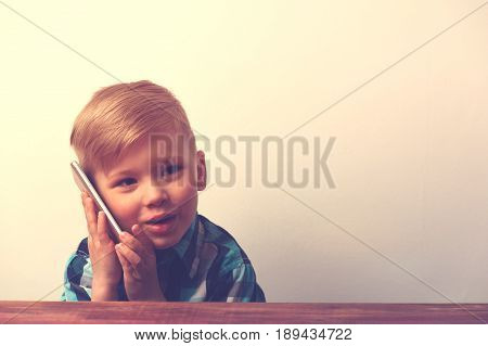 Little smiling caucasin boy sitting at the table and talking on the phone. Cute child using smartphone. Technology concept.