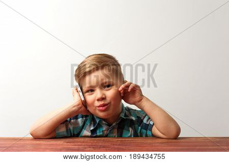 Modern digital gadget in kid's hands. Smiling little boy sitting at the table and talking on the phone. Cute caucasian child using smartphone.