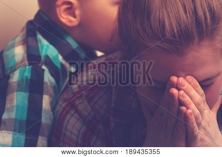 Crying unhappy woman covering her face with hands while little child standing next to her. Tired and depressed mother with kid at home. Family relations problems.