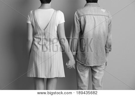 Young lesbian couple holding hands together on gray background