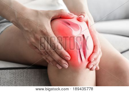 Health care concept. Woman suffering from pain in knee, closeup