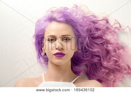 Lilac color for trendy hairstyle ideas. Young woman with dyed hair on white wooden background