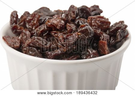 A ramekin filled with dried cherries on white