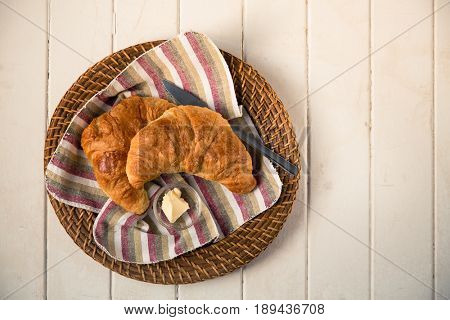 Warm croissants, served on an wicker serving plate with a striped napkin, over old wood painted table. Overhead view with vintage style processing.