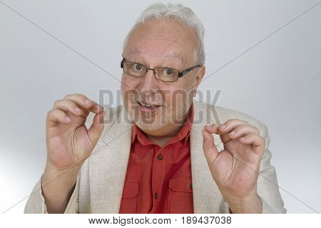 White-haired man with glasses shows OK sign with fingers- on bright background