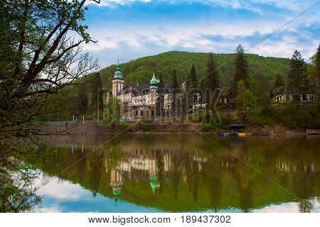 Northern front of Lillafured palace in Miskolc, Hungary. Lake Hamori in foreground with reflections. Travel outdoor landmark background