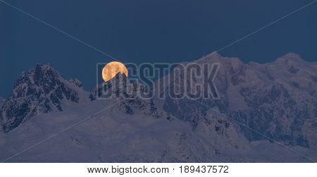 The moon emerges from behind the mountains in Denali