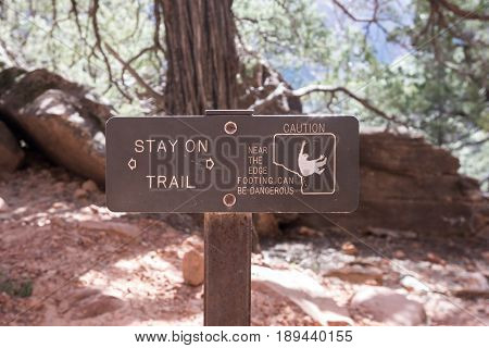 Stay On Trail Warning Sign on cliffside trail