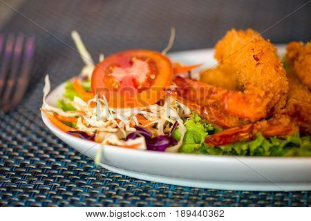 Large Shrimp In Batter With Vegetables On A Plate Close Up
