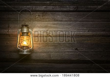 Oil lamp at night on a wooden wall