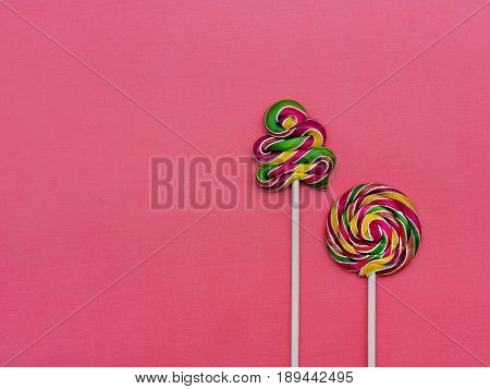 Two colorful lollipops on a pink background Round lollipop and a spiral lollipop
